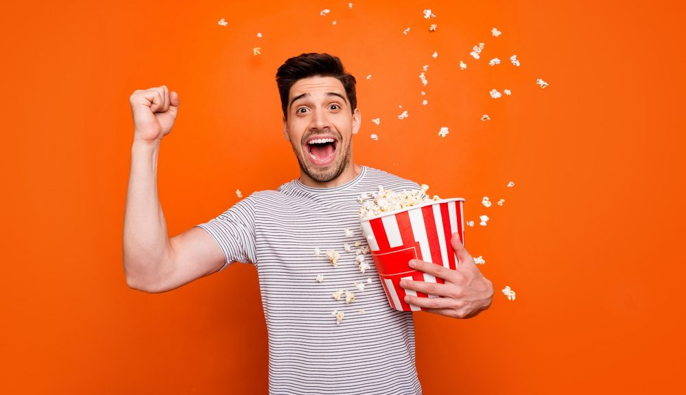Photo of attractive crazy funky guy watch television humor show eat popcorn raise fist glad series beginning wear striped t-shirt isolated bright orange color background